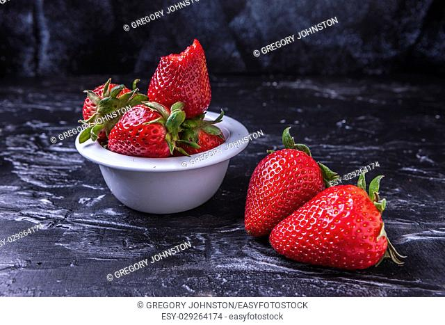 A close up of ripe strawberries in a small bowl and on the table