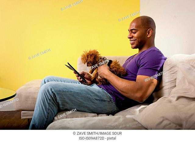 Mid adult male sitting on sofa with dog looking at digital tablet