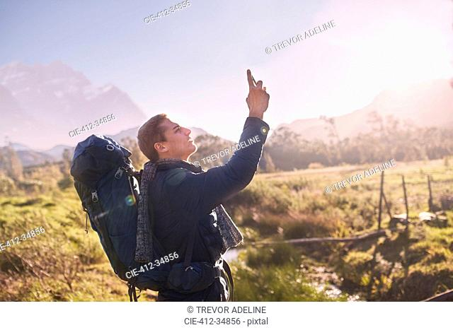 Young man with backpack hiking and using camera phone in sunny, remote field