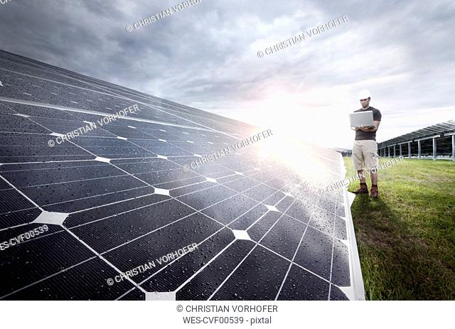 Engineer with laptop checking solar plant at evening twilight