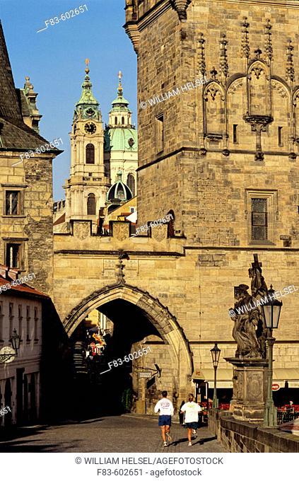 Mala Strana area: Charles Bridge Tower, St. Nicholas Church, joggers. Prague. Bohemia. Czech Republic