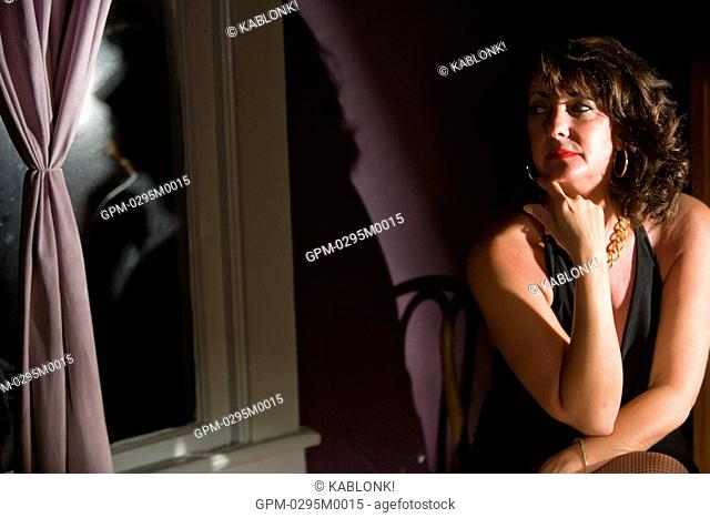 Portrait of thoughtful mid adult woman sitting in house looking out window