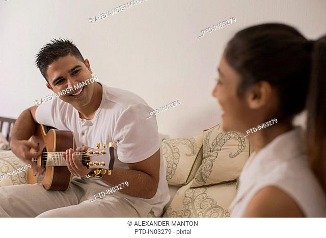 Singapore, Young man playing guitar and looking at young woman