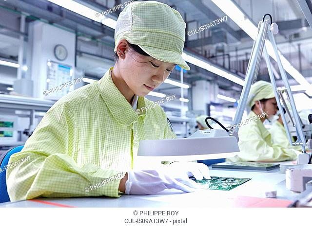 Young woman working at quality check station at factory producing flexible electronic circuit boards. Plant is located in the south of China, in Zhuhai