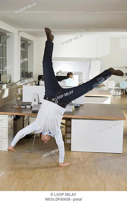 Germany, Munich, businessmen in office, one of them doing cartwheel