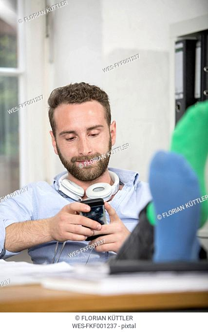 Young man in office with feet on desk looking at cell phone