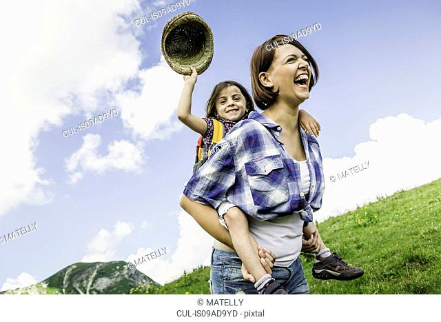 Mother and daughter on hike, girl holding straw hat