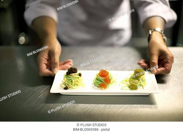 Chef holding plate of Japanese food