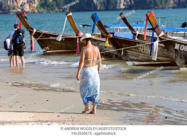 Woman in sun hat bikini and sarong walks beach by longtail boats Ao Nang Thailand