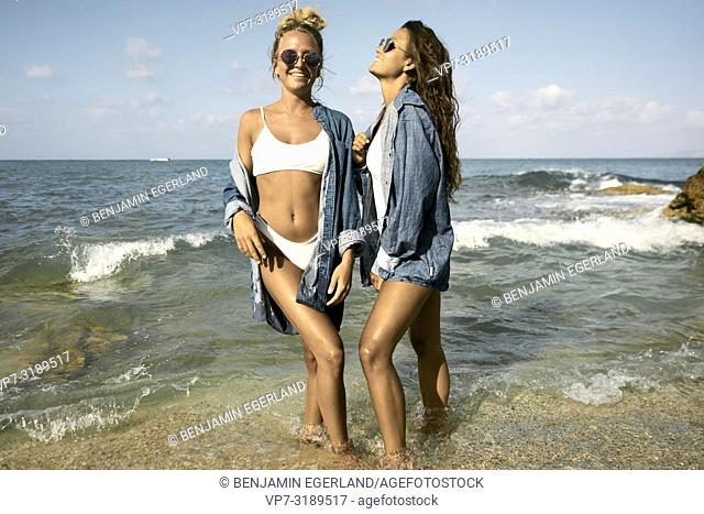 Two women standing in water at beach, Chersonissos, Crete, Greece