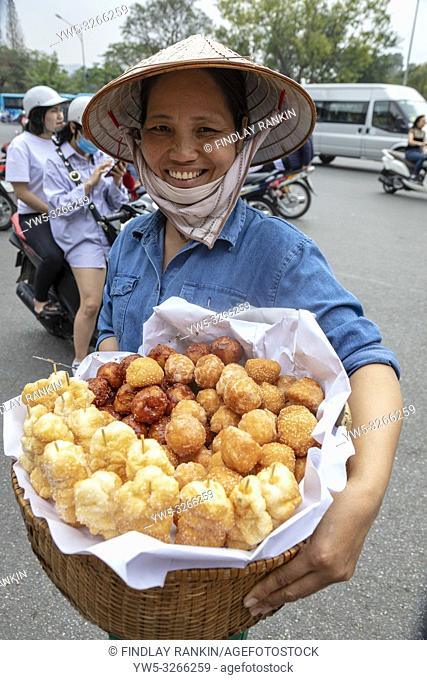 Woman selling pastries and deep fried vegetables from a wicker basket on the street, Hanoi, Vietnam, Asia