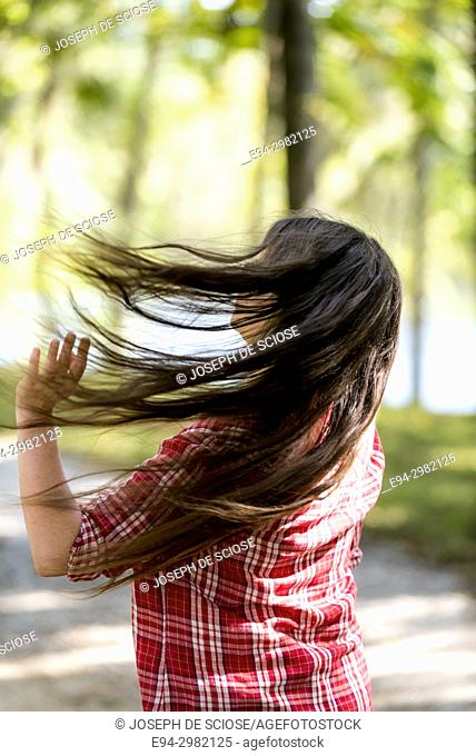Back view of a young woman swishing her long brown hair