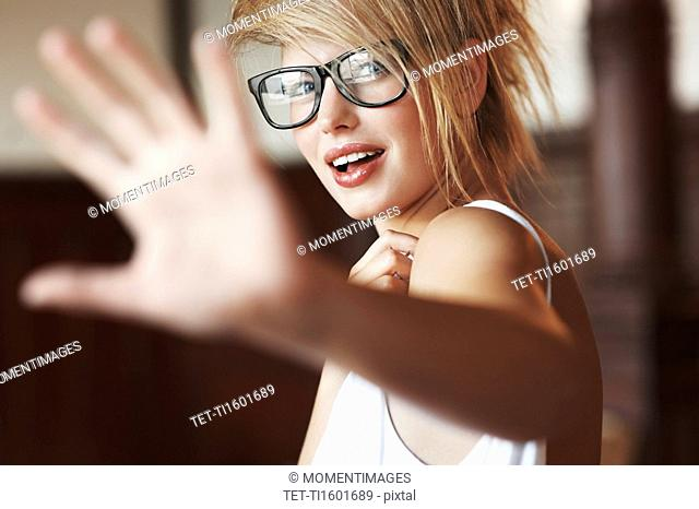 Blond woman holding her hand out