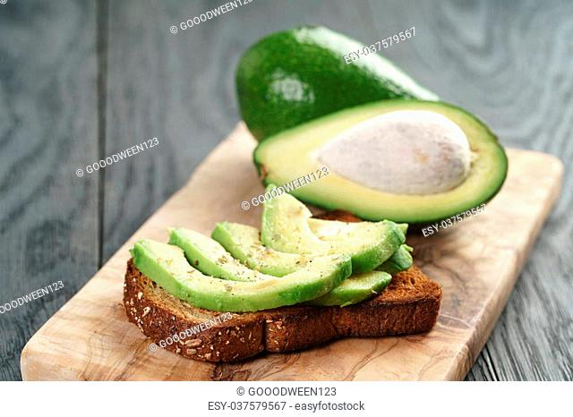 rye toast with sliced avocado and herbs, simple rustic sandwich
