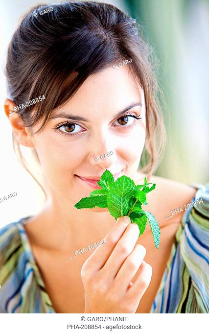 Woman smelling mint leaves Mentha sp
