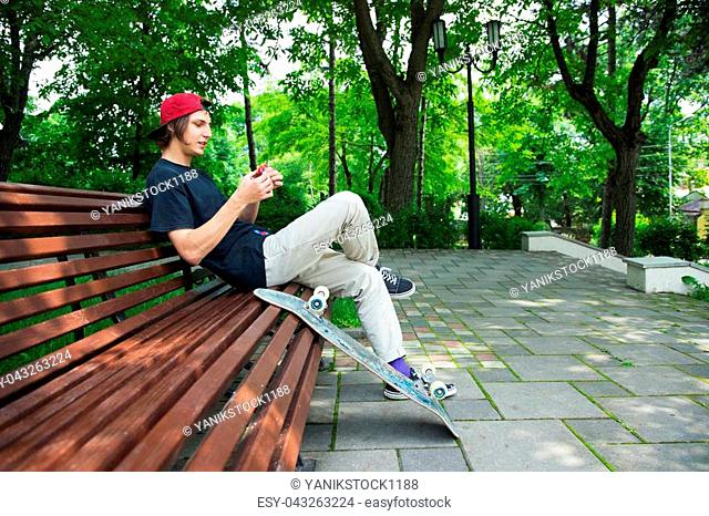 4c638f08334 A long-haired hipster skater in a cap sits on a bench and turns a