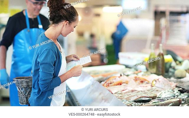A friendly fishmonger coming over to assist a female customer choose the best fresh fish