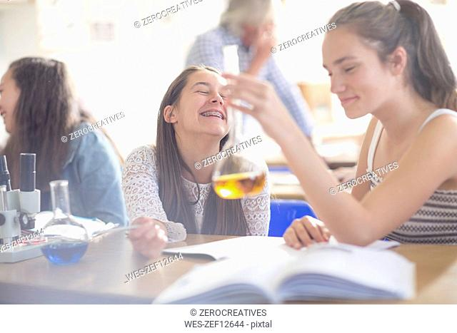Happy teenage girls in high school chemistry class experimenting