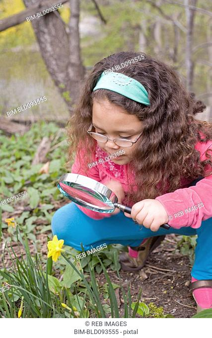 Hispanic girl looking at flower with magnifying glass