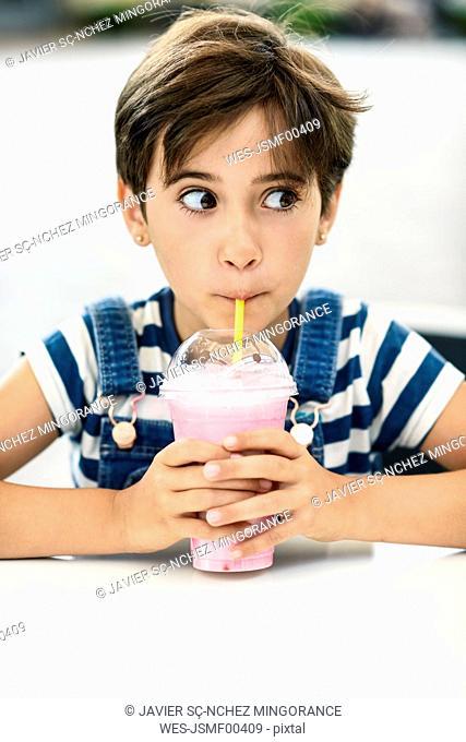 Portrait of little girl drinking strawberry milkshake at pavement cafe