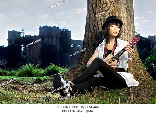 Thai woman playing guitar in park