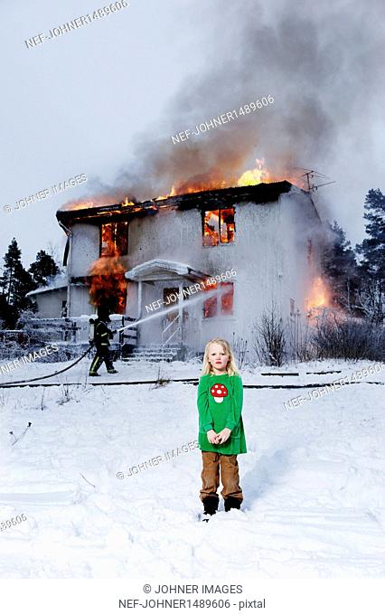 Girl in front of burning building, fireman in background
