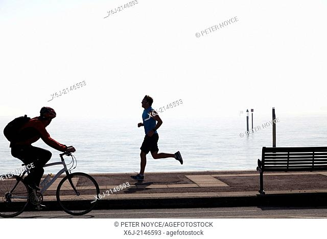 Cyclist and jogger on Southsea Promenade