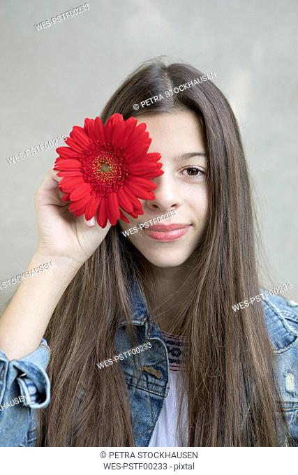 Portrait of smiling girl with flower head of red Gerbera