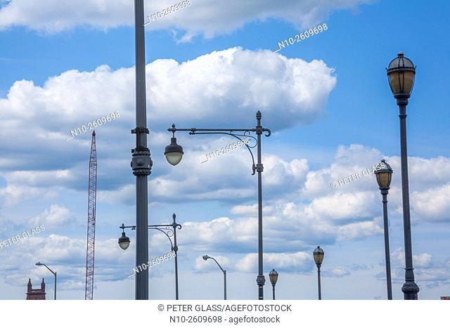 Streetlamps and a crane in front of a cloudy sky