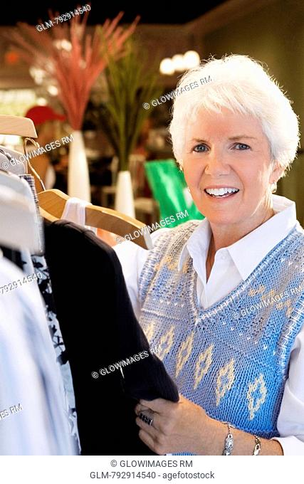 Portrait of a senior woman choosing clothes in a clothing store