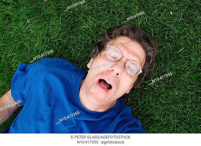 Middle age man, wearing glasses and eyes closed, lying on the grass in a park