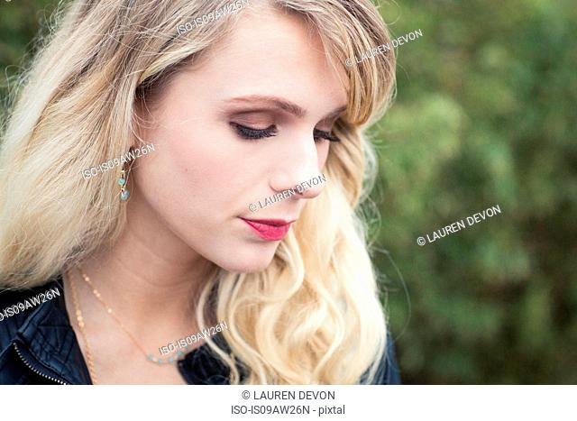 Portrait of young blonde haired woman looking down