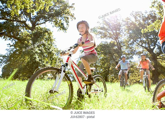Family riding mountain bikes in rural field