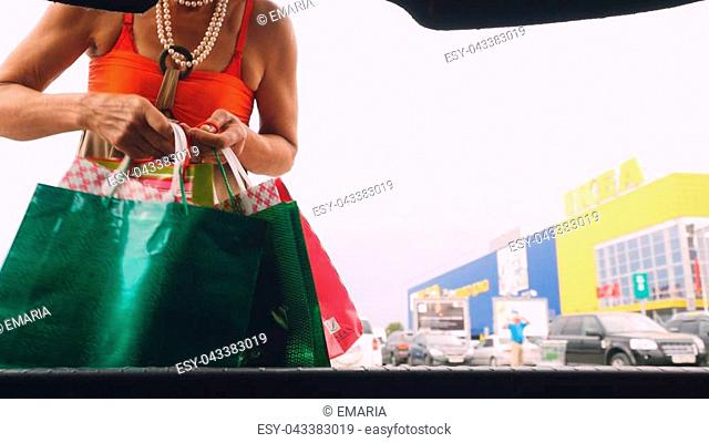 Young happy woman putting shopping bags into car trunk outdoor at shopping mall