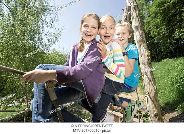 Girls sitting on suspension bridge in playground, Munich, Bavaria, Germany
