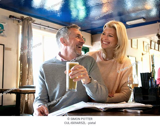 Couple laughing and reading newspaper in pub