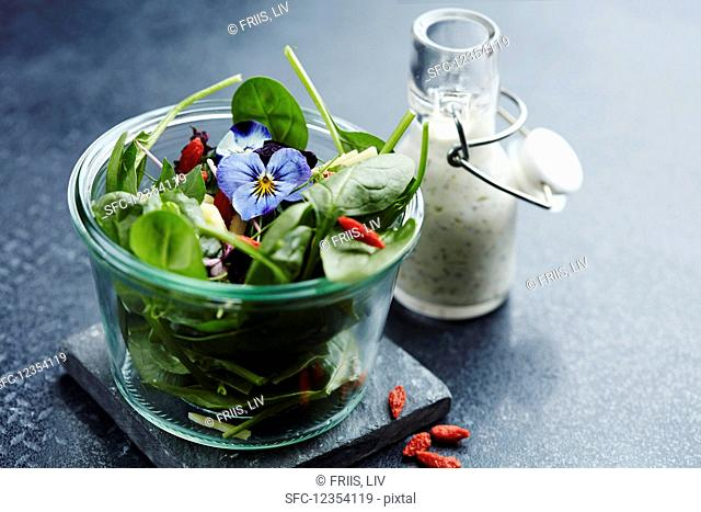 Spinach salad with goji berries, pansies, and a yogurt dressing