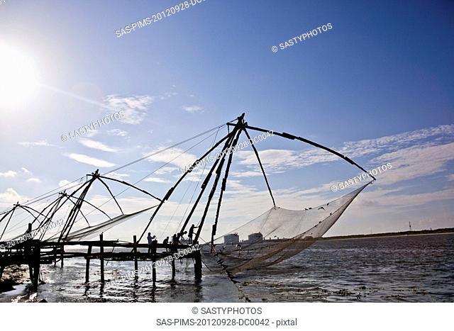 Fishermen with Chinese fishing nets at a harbor, Cochin, Kerala, India