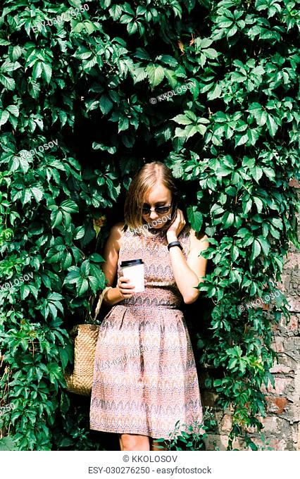 Portrait of adult brunette woman in sunglasses and dress with coffee to go looking down against of green hedge in sunlight
