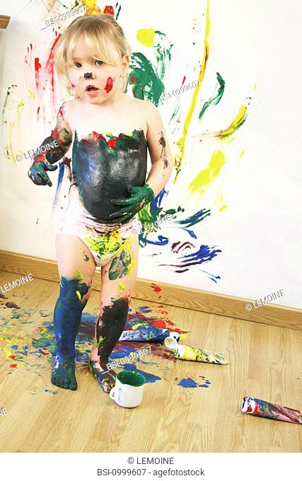 Model. 2-and-a-half-year-old girl painting on a wall