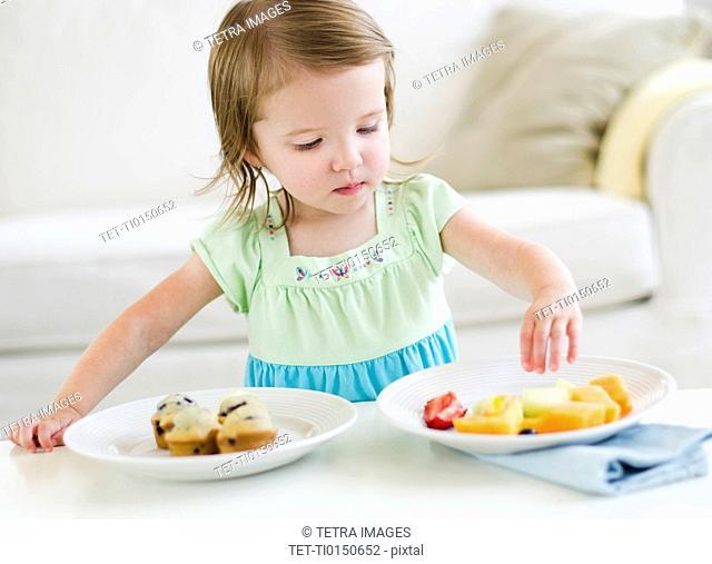 Girl 2-3 choosing between fruit salad and muffins