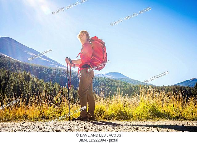 Caucasian hiker with backpack standing near mountains