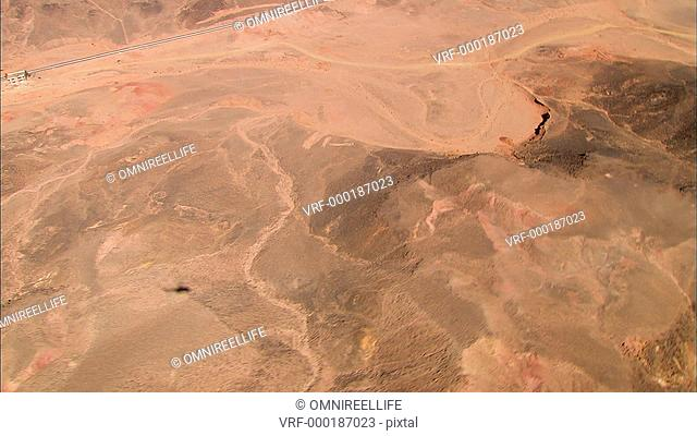 Aerial view of road winding through desert landscape with mountains and helicopter shadow