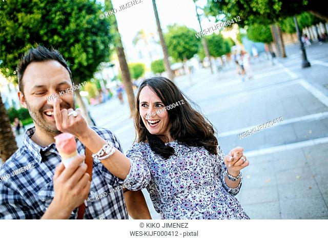 Couple having fun while eating an ice cream cone