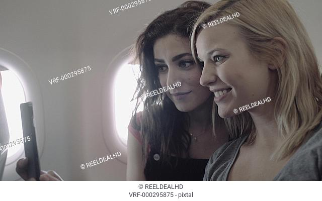 Young adult women on airplane taking photograph with mobile phone