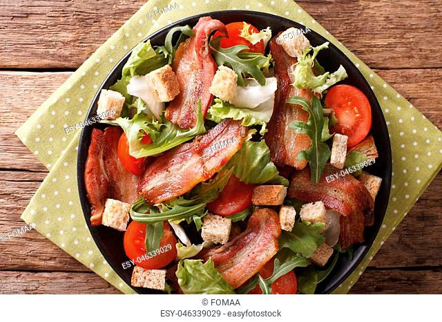 Mix salad of fried bacon, tomato, croutons and lettuce close-up on a plate on a table. horizontal view from above