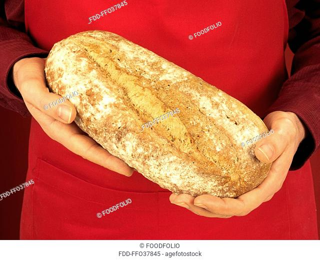 Man Holding Crusty White Bread