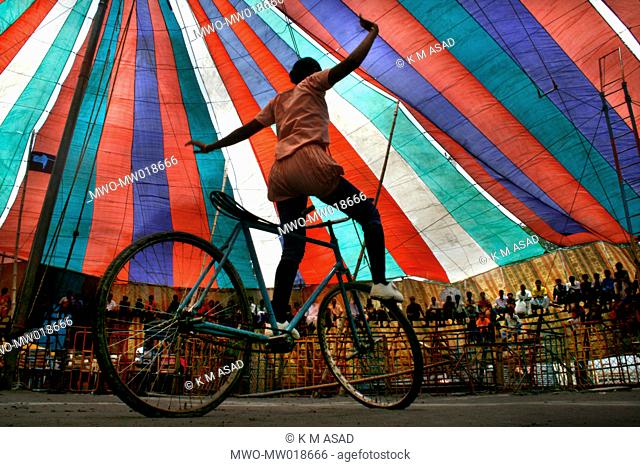 A woman performs acrobatics with a bicycle, in a circus show, in Dhamrai, Dhaka, Bangladesh July 11, 2008
