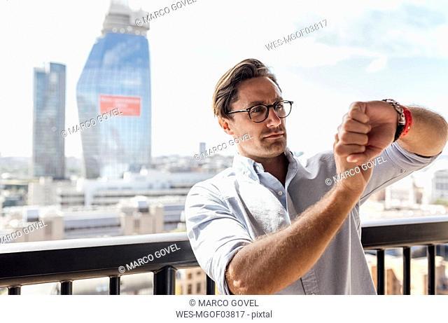 UK, London, man using smartwatch on a roof terrace