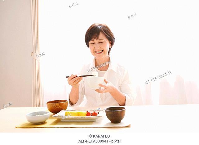 Senior adult Japanese woman eating